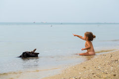 Naked little girl plays in the sea, beautiful beach Royalty Free Stock Photography