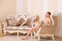 Naked macho man sitting on retro chair. Stock Images