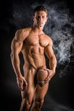 Naked male bodybuilder hiding crotch with american football ball Royalty Free Stock Photos