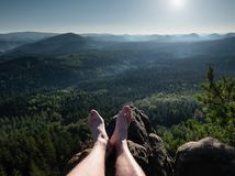 Naked male hairy legs take rest on peak. Outdoor activities in summer Stock Images