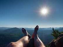 Naked male hairy legs take rest on peak. Outdoor activities in summer Royalty Free Stock Image