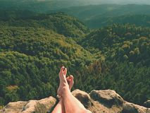Naked male legs on peak make step. Sandstone rock above valley with tired hikers legs without shoes. Stock Image