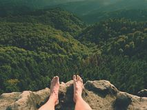 Naked male legs on peak make step. Sandstone rock above valley with tired hikers legs without shoes. Outdoor activities in hot summer muggy weather Royalty Free Stock Images