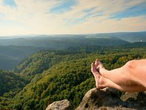 Naked male legs on peak make step. Sandstone rock above valley with tired hikers legs without shoes. Stock Images