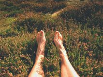 Naked male legs on peak make step. Sandstone rock above valley with tired hikers legs without shoes. Outdoor activities in hot summer muggy weather Royalty Free Stock Photos