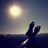 Naked male legs take rest on peak. Outdoor activities Royalty Free Stock Images
