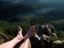 Naked male legs take rest on peak. Outdoor activities Stock Images