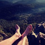 Naked male legs take rest on peak. Outdoor activities Royalty Free Stock Photos