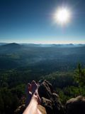 Naked male legs take rest on peak. Outdoor activities Royalty Free Stock Photography