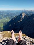 Naked male sweaty legs in dark hiking trousers take a rest on peak of mountain above spring valley. Stock Image
