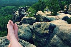 Naked male sweaty long legs on peak of sharp rock above valley. Stock Image
