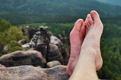 Naked male sweaty long legs on peak of sharp rock above valley. Royalty Free Stock Images