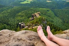 Naked male sweaty long legs on peak of sharp rock above valley. Royalty Free Stock Photos