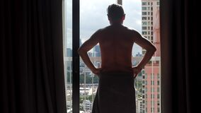 Naked man approaches window and opens curtains