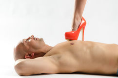 Naked man being stepped on. A naked men lying on the floor while a women steps on his chest with a red stilletto Royalty Free Stock Photos