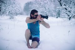 Naked man with camera stand in the winter forest. Naked man make some photo in the winter snowy forest Stock Photography