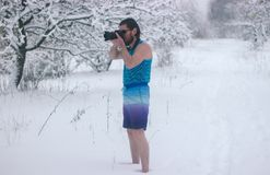 Naked man with camera stand in the winter forest. Naked man make some photo in the winter snowy forest Stock Photo