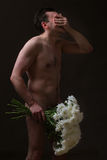 Naked man with flowers Stock Photos