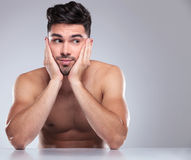 Naked man with head in his palms looking to side Stock Photo