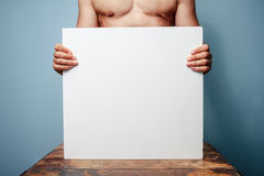 Naked man holding a white board Royalty Free Stock Image