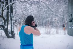 Naked man with camera stand in the winter forest. Naked man make some photo in the winter snowy forest Stock Photos
