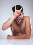 Naked man making a rock and roll hand sign Stock Photo