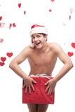Naked man in santa hat holding christmas gift