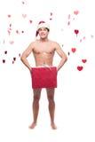 Naked man in santa hat holding christmas gift Stock Image