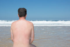 Naked man is sitting cross legged on an empty beach and meditating. stock photography