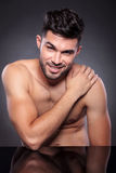 Naked man smiles with hand on shoulder Royalty Free Stock Image