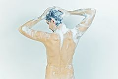 Naked man taking a shower in the foam Royalty Free Stock Photo