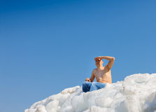 Naked man on top of the ice mountain against Stock Images