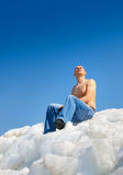 Naked man on top of the ice mountain against Royalty Free Stock Photography
