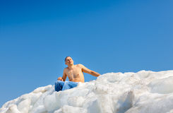 Naked man on top of the ice mountain against Stock Photo