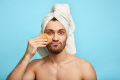 Naked man using sponge for cosmetic procedure stock images