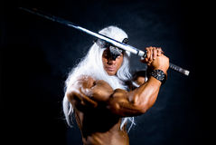 Naked muscular man warrior with a sword. Royalty Free Stock Images