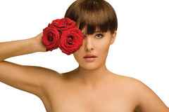 Naked roses. Studio portrait of a pretty woman holding three red roses in front of her face stock image