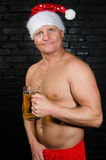 Naked Santa with beer in hand. Christmas and party. Adult naked man drinks beer Royalty Free Stock Photography
