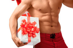 Naked sexy Santa showing presents he has. Those abs. Cropped closeup of a sexy male torso Royalty Free Stock Photo
