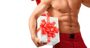 Naked sexy Santa showing presents he has. Best Santa. Horizontal cropped studio closeup of a man with stunning fit body with abs holding a present Stock Photos