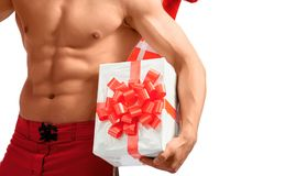 Naked sexy Santa showing presents he has. Taking this with me. Studio closeup shot of a ripped and toned young man holding Christmas gifts near his perfect abs Stock Photos