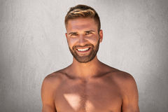 Naked smiling man with stylish hairdo, charming dark eyes and bristle, having good mood while posing against grey concrete wall. H Royalty Free Stock Image