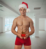 Naked still muscular men wearing christmas cup holding small red Stock Photography