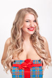 Naked to the waist beautiful blonde with big breasts standing on. A white background and holding a gift and smiling at the camera, selective focus on the tablet Stock Image