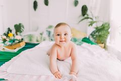 The naked toddler is lying on the bed and looking at the camera. Royalty Free Stock Photos