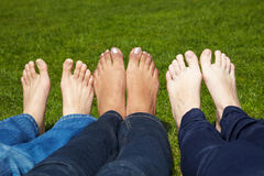 Naked toes in a park. Three women with naked feet lying in grass Stock Photo
