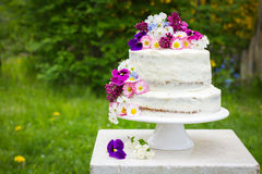 Naked wedding cake. Decorated with spring flowers, selective focus Royalty Free Stock Image