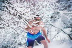 Naked wild man in glasses hiding the winter snowy forest Royalty Free Stock Images