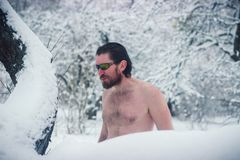 Naked wild man in sunglasses the winter snowy forest Stock Photo