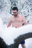 Naked wild man in sunglasses the winter snowy forest Royalty Free Stock Image
